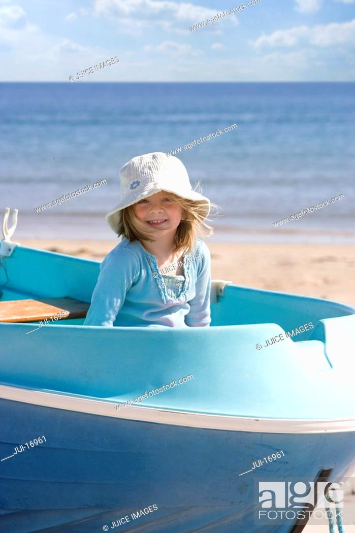 Stock Photo: Portrait of girl sitting in rowing boat on beach.