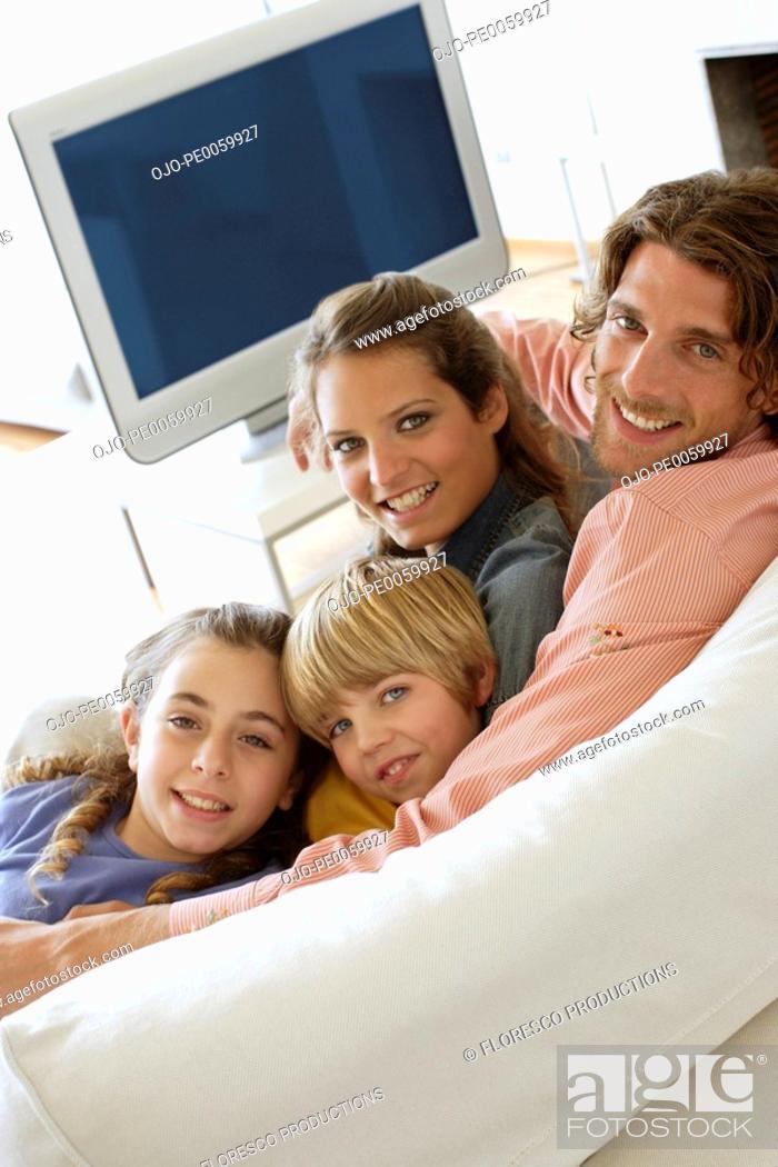 Stock Photo: Family in living room on sofa bonding.