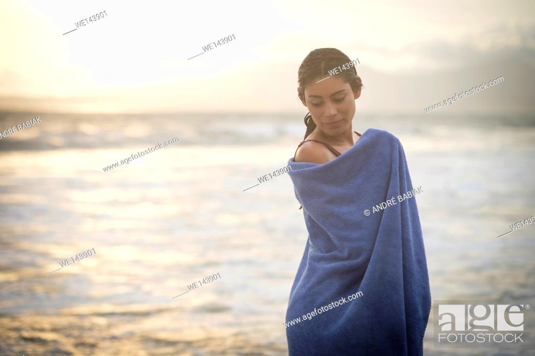 Stock Photo: Sunset portrait of young hispanic woman wrapped in a towel at a beach.