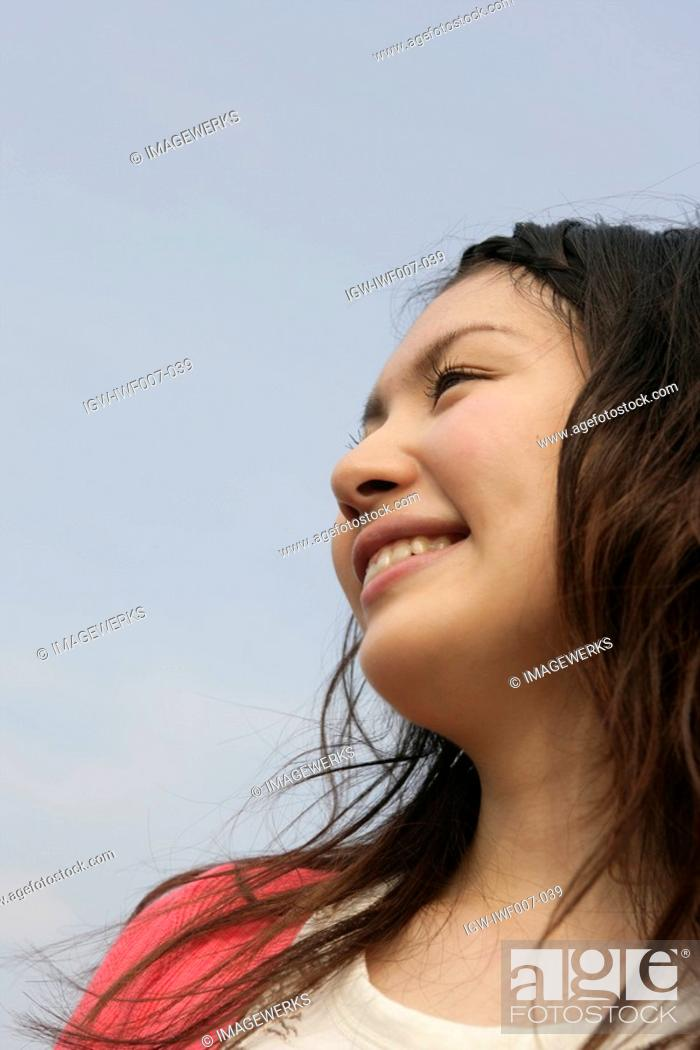 Stock Photo: A young woman is seen under the sky as she smiles heartily.