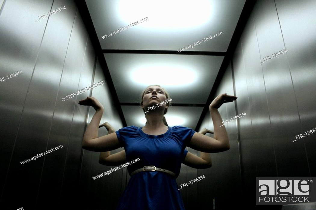 Stock Photo: Young woman posing in elevator.
