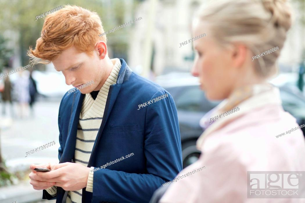 Stock Photo: Man text messaging on a mobile phone with her girlfriend beside him.