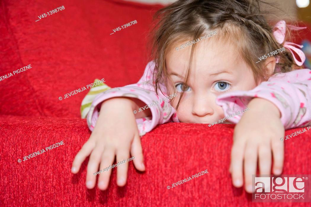 Stock Photo: 4 years old girl in pink pyjama lying on red sofa bed.