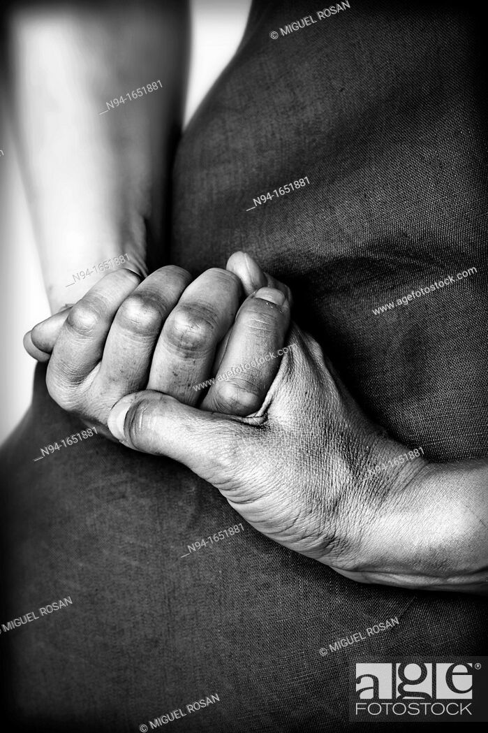 Stock Photo: Close up of black and white hands clasped woman.
