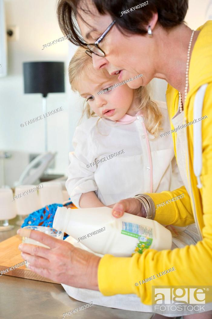 Stock Photo: Elderly woman pouring milk into a glass for her granddaughter.
