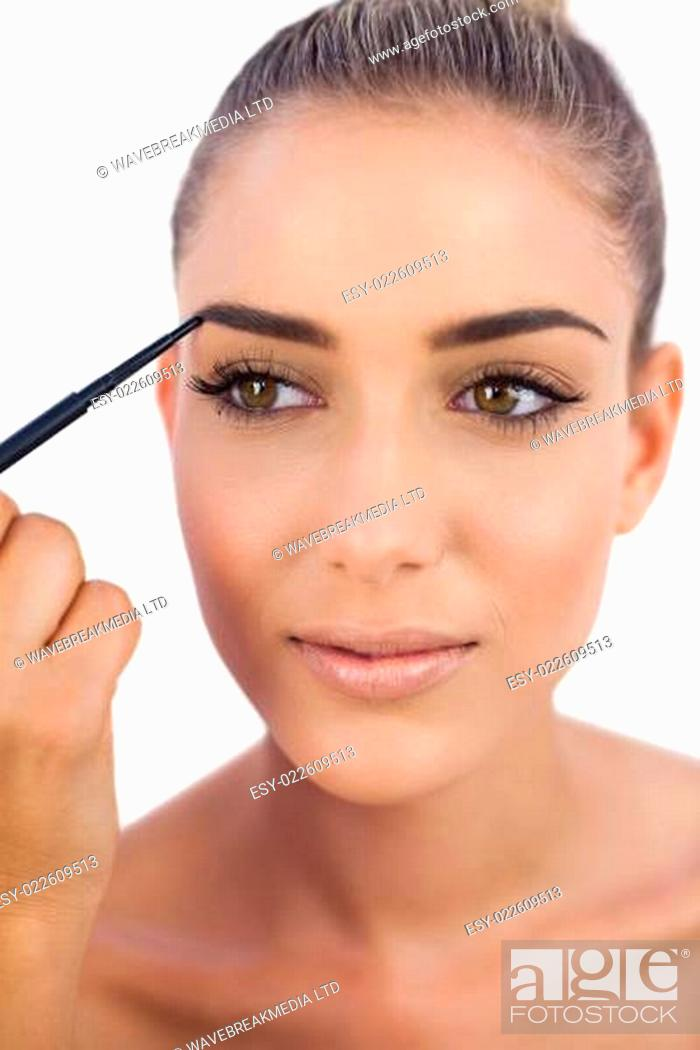 Stock Photo: Smiling woman applying make up on her eyebrows.