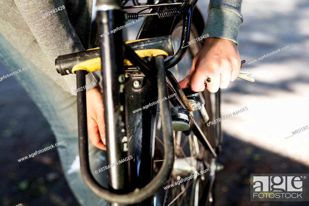 Photo de stock: Cropped hand of woman locking bicycle.