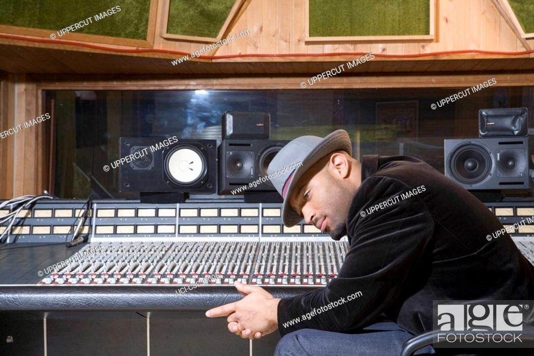 Stock Photo: Music producer listening to music in studio.