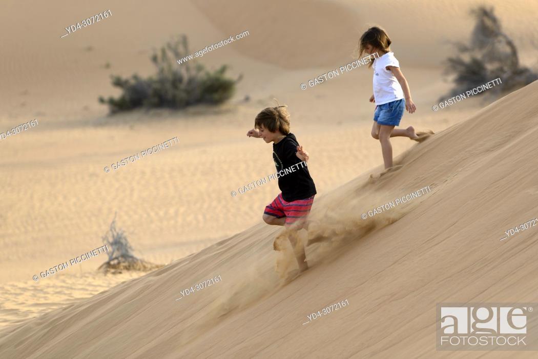 Stock Photo: Boy and girl running in the sandune, desert, Dubai, United Arab Emirates.