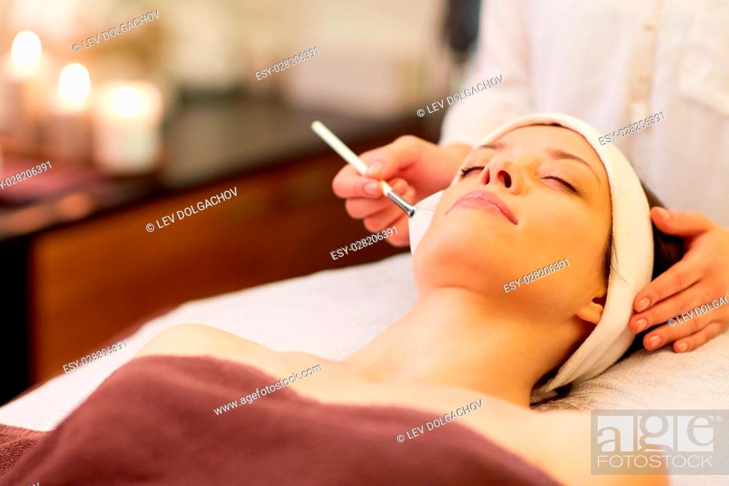 Stock Photo: people, beauty, cosmetology and treatment concept - close up of beautiful young woman lying with closed eyes and cosmetologist applying facial mask by brush at.