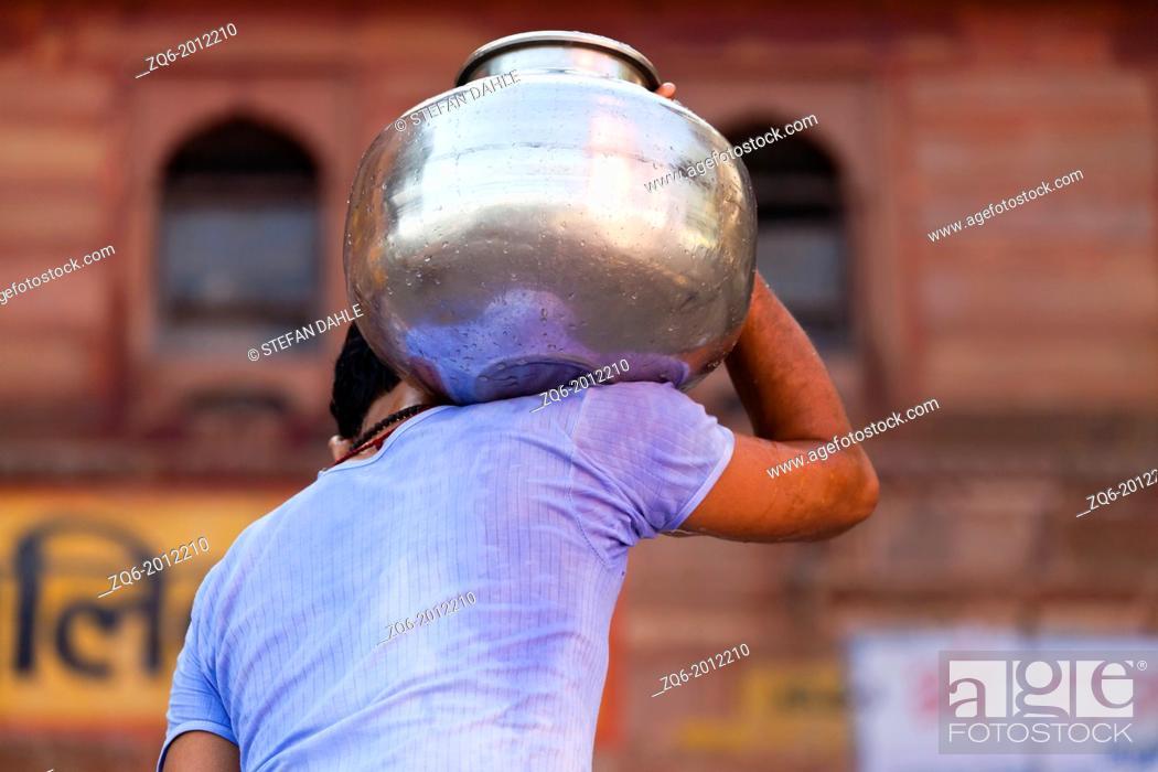 Stock Photo: Man carrying Metal Container in Varanasi, India.