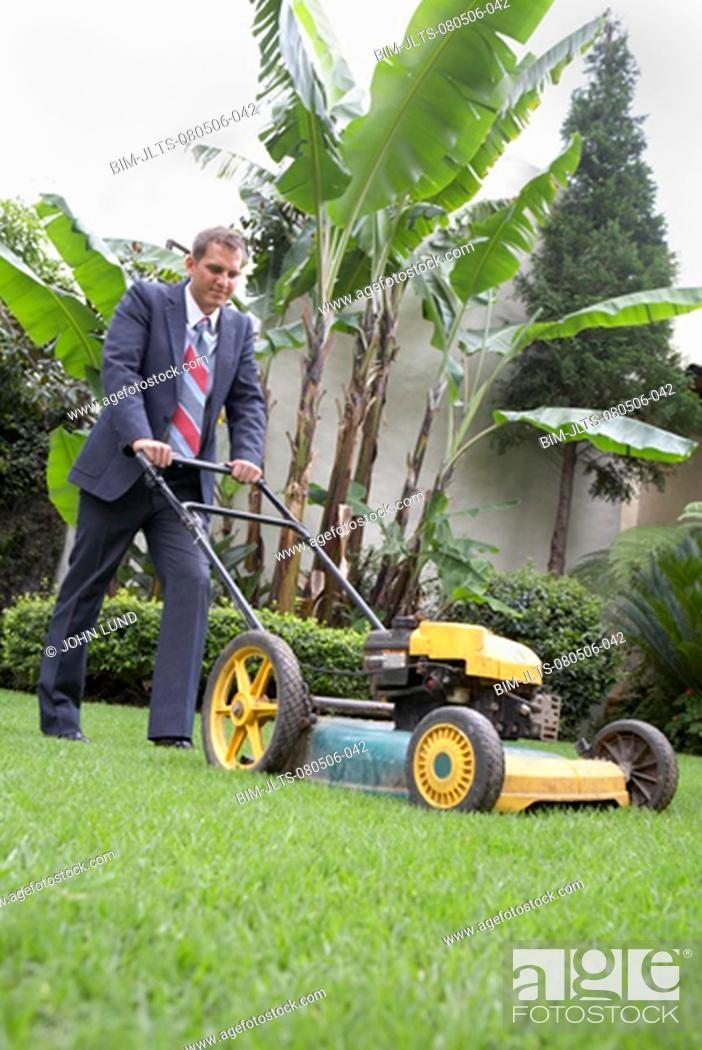 Stock Photo: Hispanic businessman pushing lawn mower.