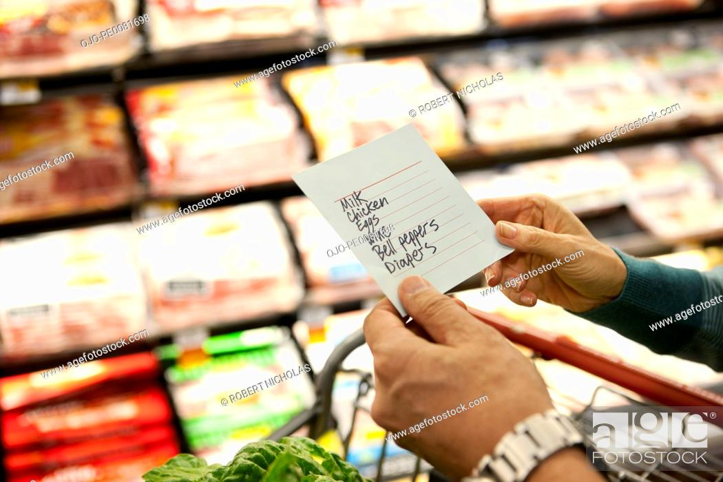 Stock Photo: Older woman reading grocery list in supermarket.