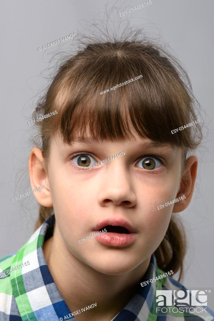 Stock Photo: Portrait of a very surprised ten year old girl with bulging eyes and open mouth, European appearance, close-up.