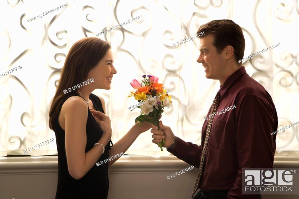 Stock Photo: Man surprised woman with bouquet.