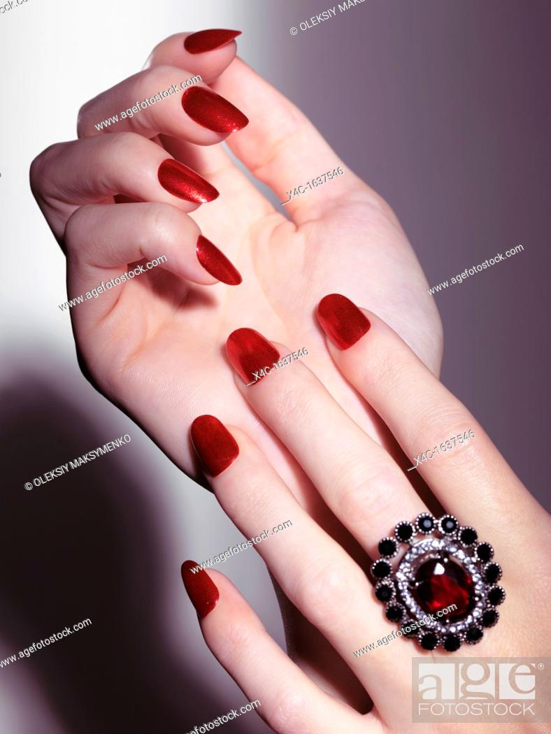 Stock Photo: Closeup of woman hands with shiny red nail polish and a red stone ring.