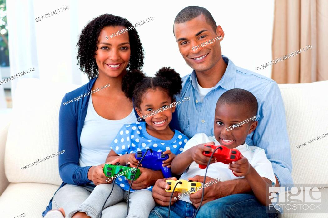 Stock Photo: Smiling Afro-american family playing video games.