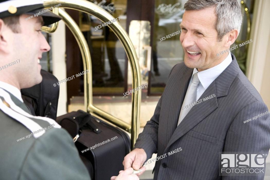 Stock Photo: Businessman tipping bellhop.