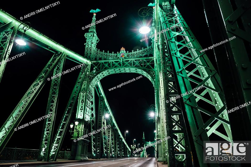 Imagen: Old Iron Bridge at night in the light of streetlights across the Danube River in Budapest Hungary.