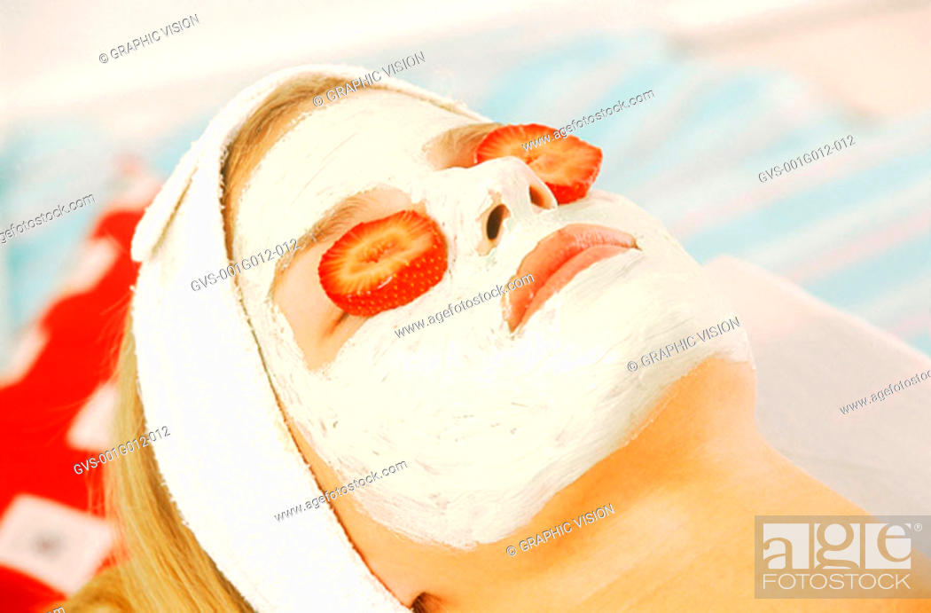 Stock Photo: Close-up of a woman with a pack and strawberry slices on her face.