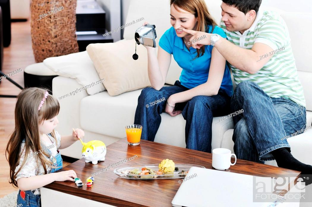 Stock Photo: young happy family recording by video camera their child at home.