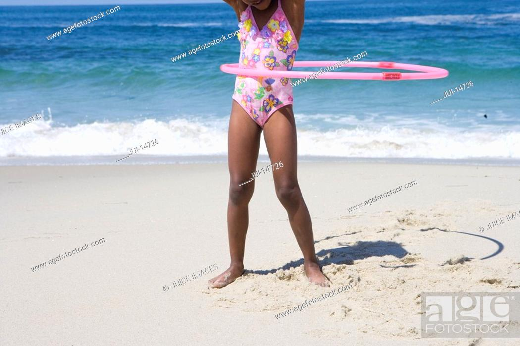 Stock Photo: Girl 4-6 playing with plastic hoop on beach, low section.