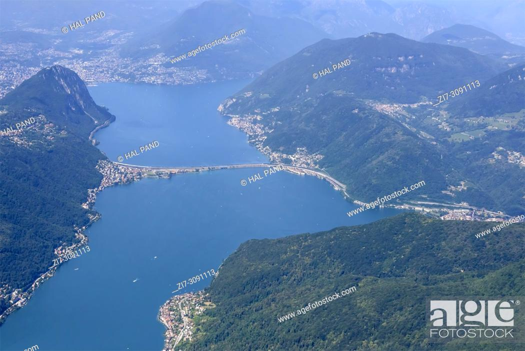 Imagen: aerial shot, from a small plane, of dam bridge on Lugano lake , shot on a bright early summer day at Melide, Ticino, Switzerland.