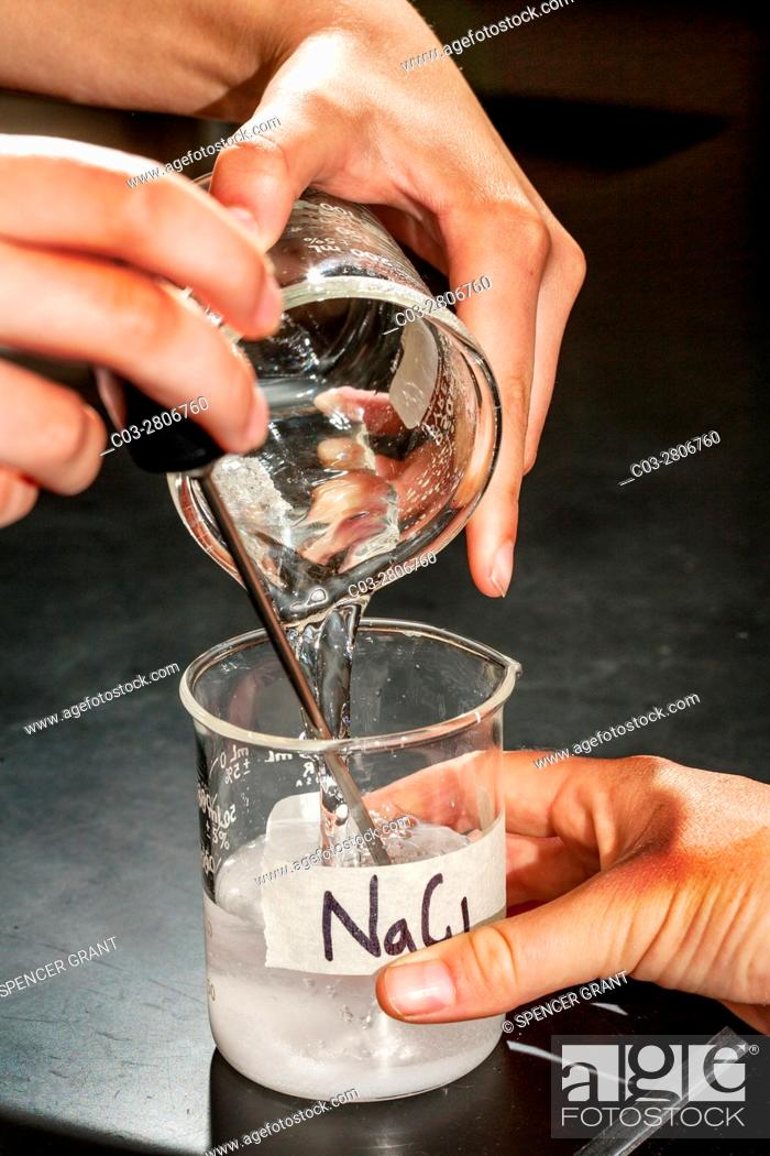 Stock Photo: A beaker of water is poured into dry sodium chloride powder during an experiment in a San Clemente, CA, solution chemistry lab.