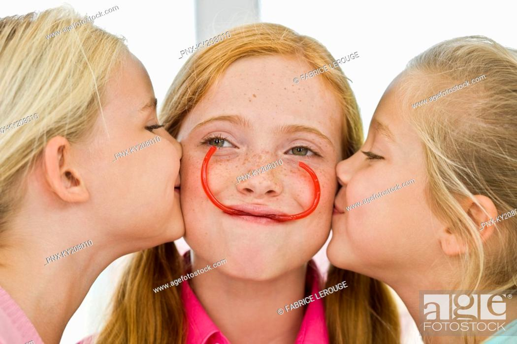 Stock Photo: Close-up of two girls kissing their friend.