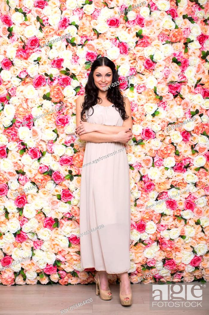 Stock Photo: Full length portrait of a beautiful young brunette woman in a studio on a floral wall background.