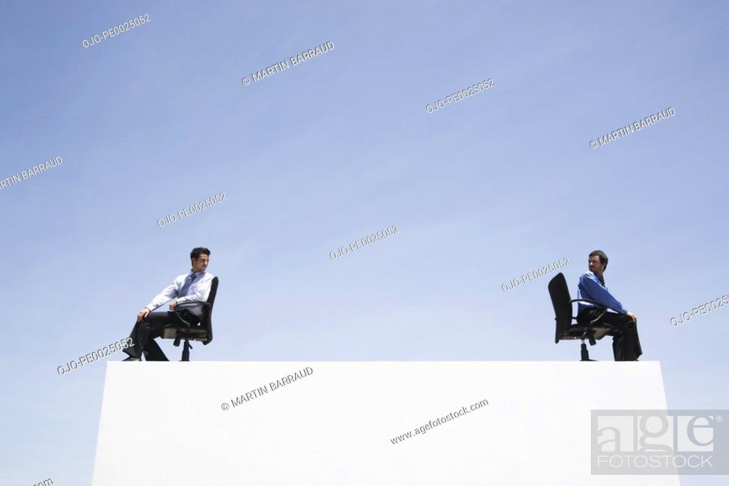 Stock Photo: Two businessmen in office chairs on wall outdoors back to back.
