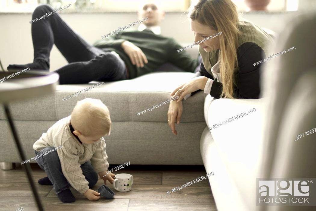 Imagen: parents with baby toddler child relaxing in living room at home, in Cottbus, Brandenburg, Germany.