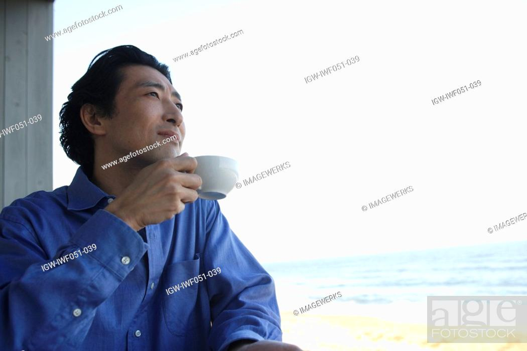 Stock Photo: Mature man drinking tea, side view.