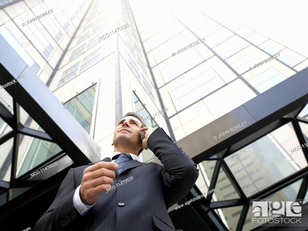Stock Photo: Businessman using mobile phone outside office low angle view.