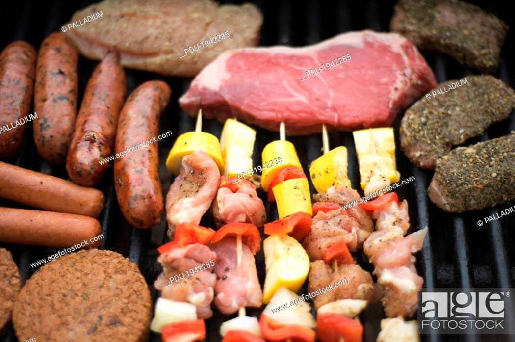 Stock Photo: Various cuts of meat, sausage, skewers, and veggie patties cook on a grill.