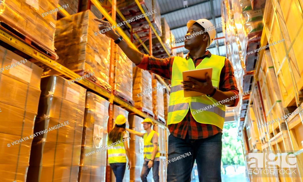 Imagen: Portrait african black warehouse supervisor standing with digital tablet check stock in large warehouse distribution center with colleague worker in background.