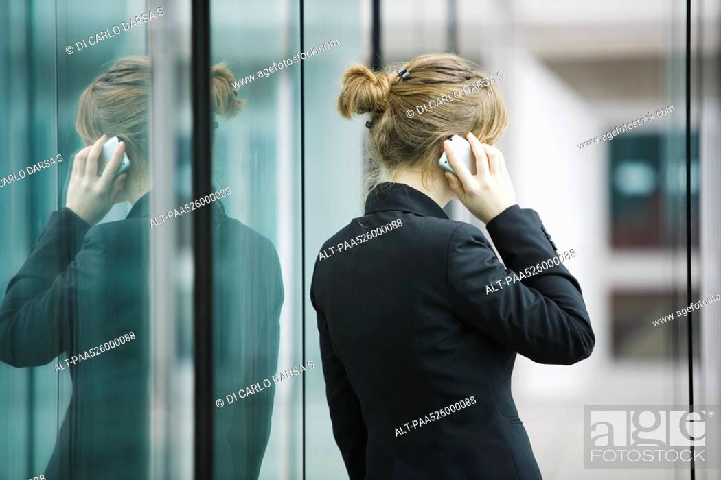 Stock Photo: Businesswoman using cell phone, rear view.