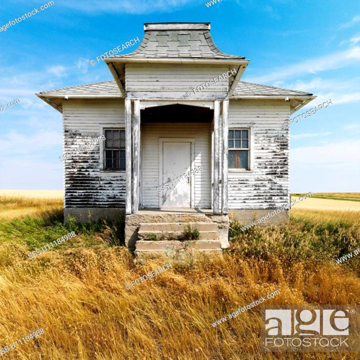 Stock Photo: Facade of weathered abandoned building with peeling paint in grasslands.
