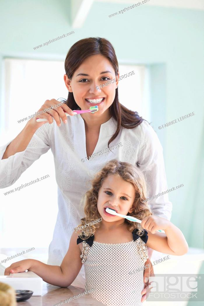 Stock Photo: Portrait of a young woman and her daughter brushing teeth.
