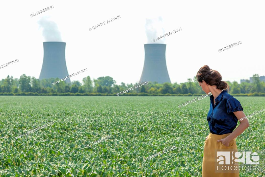 Stock Photo: Woman in soy bean filed looking behind to nuclear power station.