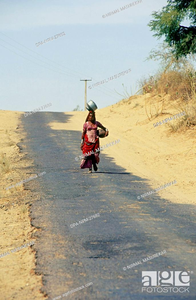 Stock Photo: woman walking for miles everyday for water ; rajasthan ; india.