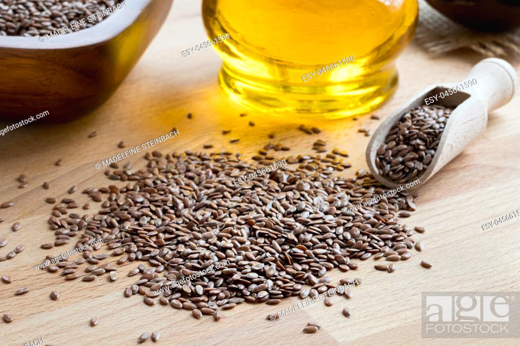 Stock Photo: Flax seeds on a wooden table, with flax seed oil in the background.