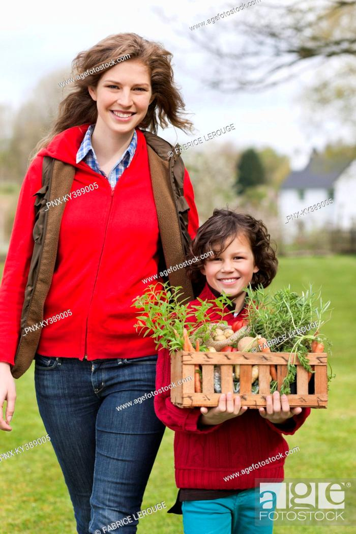 Stock Photo: Mother and son with a crate of homegrown vegetables.