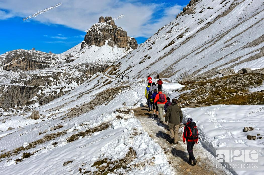 Photo de stock: Hikers on the snow-covered hiking trail of the Three Peaks Circular Walk in frotn of the Tower of Toblin, Torre di Toblin, Sesto Dolomites, South Tyrol.