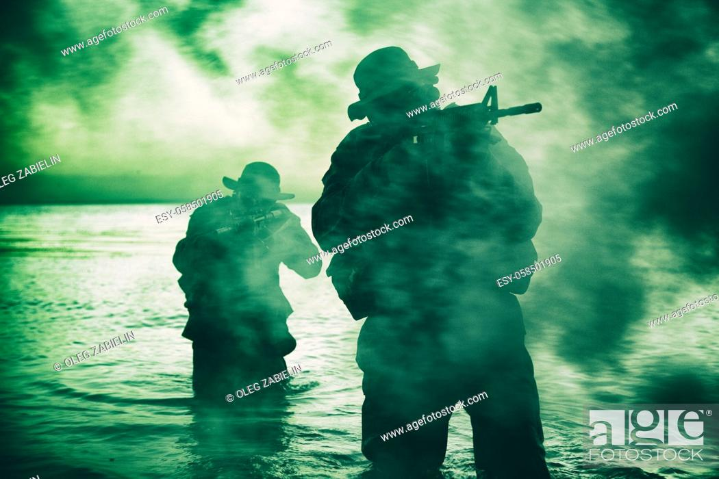 Imagen: Commando soldiers walking in water, army special operations forces fighters sneaking in darkness, aiming assault rifles and observing shore during amphibious.