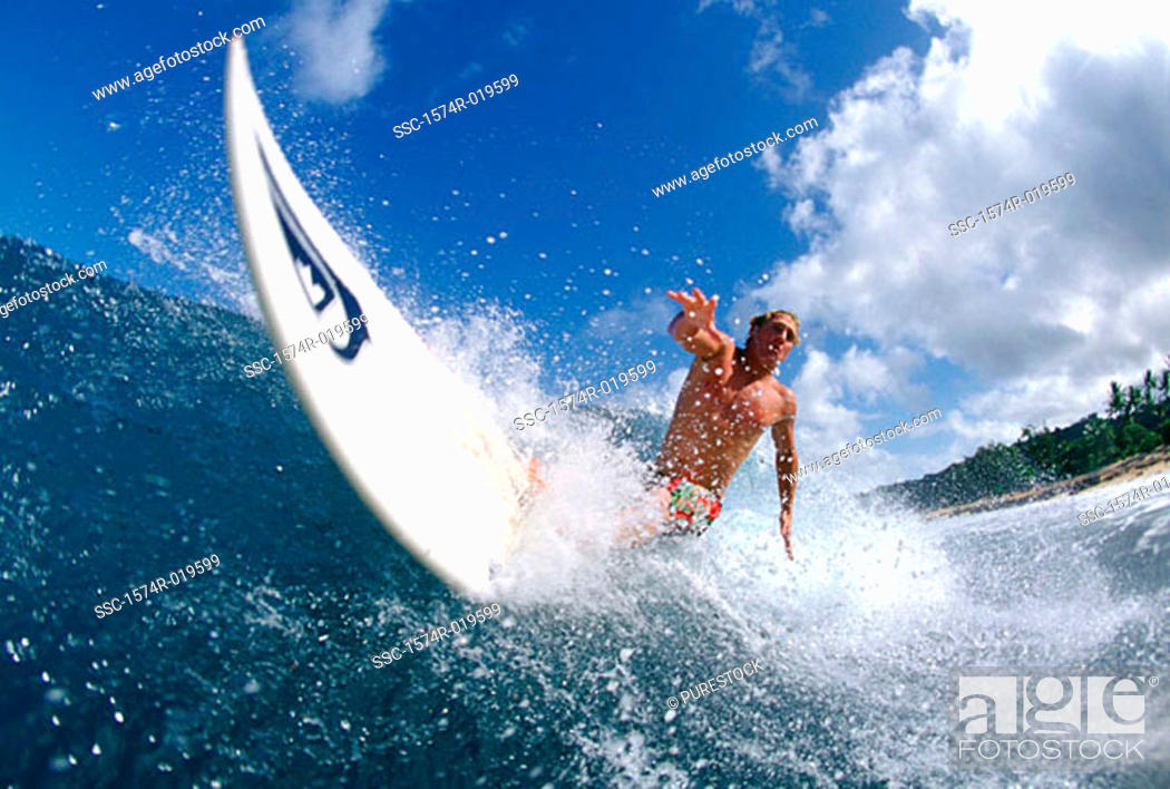Stock Photo: Low angle view of a mid adult man surfing in the sea.