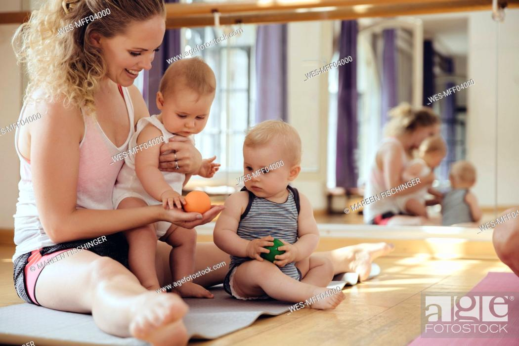 Stock Photo: Mother with playing twin babies sitting on yoga mat.