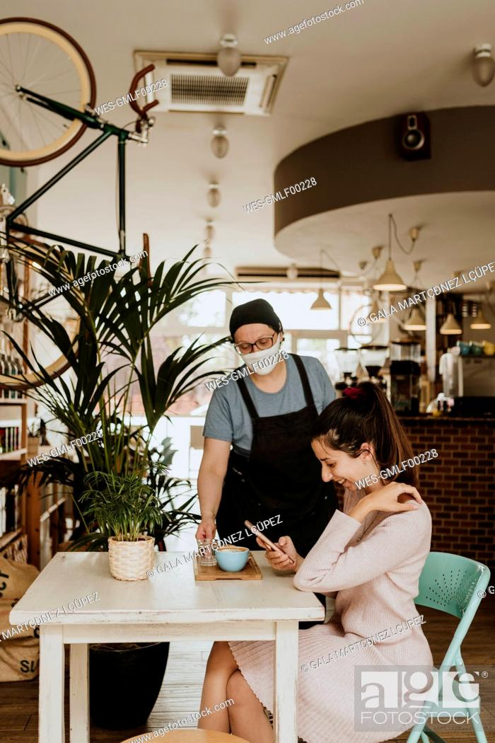 Stock Photo: Waitress with protective mask serving Cappuccino in a coffee shop.