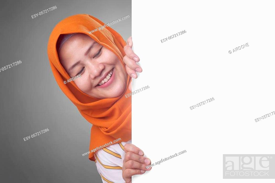 Stock Photo: Young Asian muslim businesswoman smiling and peeking behind blank white advertising billboard wign board with copy space.