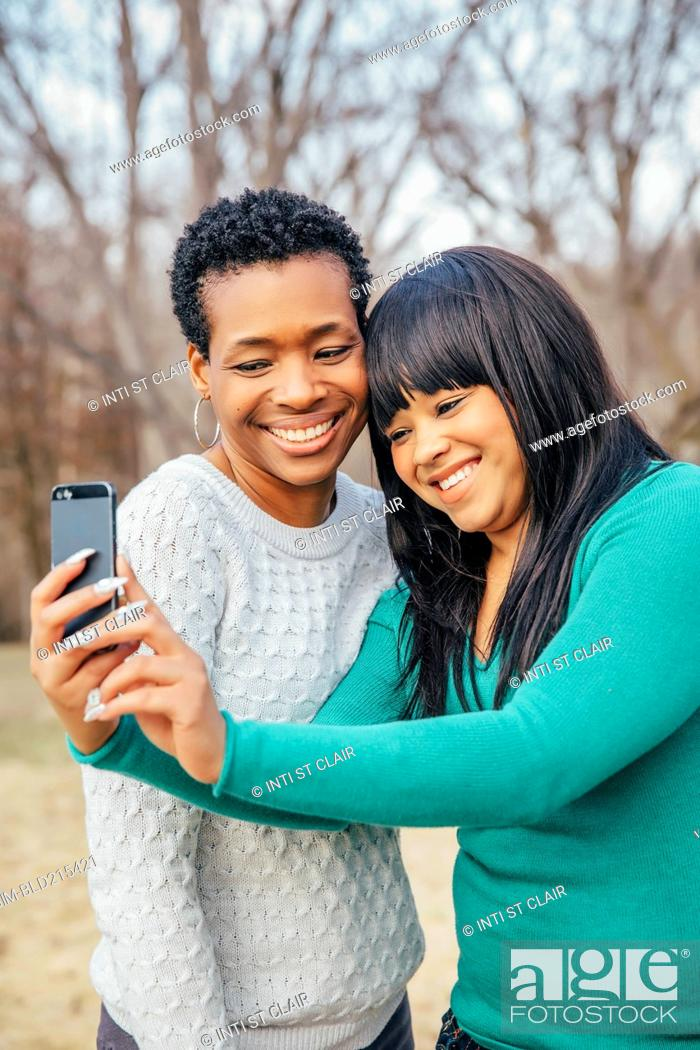Stock Photo: Black mother and daughter taking selfie outdoors.
